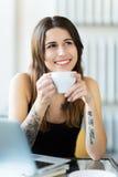 享用一杯咖啡的被刺字的妇女 免版税库存照片