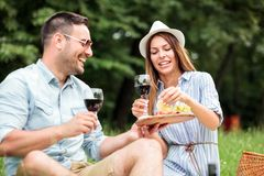 享用一杯在一顿浪漫野餐的酒的愉快的年轻夫妇在公园 免版税图库摄影