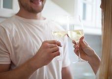 享用一杯白葡萄酒的愉快的年轻夫妇 库存照片