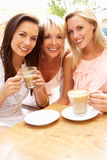 享用三名妇女的咖啡杯 免版税图库摄影