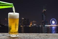 享用与夜风景的啤酒在昭披耶河,泰国 免版税图库摄影