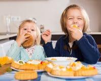 享用与奶油的两个小女孩酥皮点心 免版税图库摄影