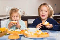 享用与奶油的两个小女孩酥皮点心 免版税库存图片