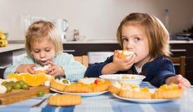 享用与奶油的两个小女孩酥皮点心 库存照片