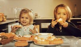 享用与奶油的两个小女孩酥皮点心 图库摄影