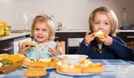 享用与奶油的两个小女孩酥皮点心 免版税库存照片