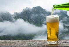 享用与山风景的啤酒 库存照片