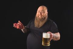 享用与快餐的肥胖人酒精饮料 免版税库存照片