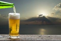 享用与日落海风景的啤酒 库存图片