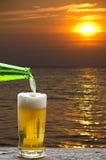享用与日落海风景的啤酒 免版税库存图片