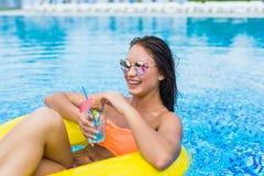 享用与橡胶环和鸡尾酒的少妇在游泳池 免版税库存图片