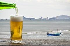 享用与海风景的啤酒 图库摄影