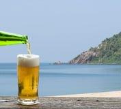 享用与海风景的啤酒 库存图片