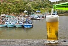 享用与渔夫村庄口岸风景的啤酒 免版税库存照片