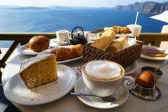 享用与爱琴海视图和早晨阳光的美丽的早餐包括热奶咖啡杯子,蛋糕,长方形宝石,新月形面包 免版税图库摄影