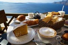 享用与美好的爱琴海视图和早晨阳光的海岛早餐包括热奶咖啡杯子,蛋糕,长方形宝石,新月形面包 免版税库存图片