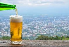 享用与都市都市风景的啤酒 免版税库存图片