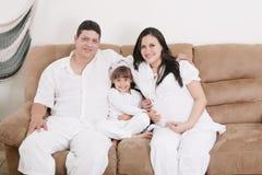 享用与他们的女儿的怀孕的夫妇 免版税图库摄影
