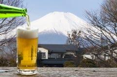 享用与Mt风景的啤酒  富士日本mt 免版税库存图片