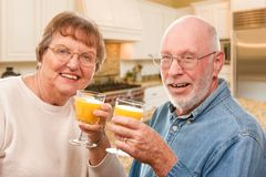 享用他们的杯橙汁的愉快的资深夫妇 免版税库存照片