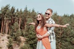享用他们的秘密隐匿处的放光的愉快的爱恋的夫妇在森林里 免版税库存图片