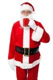 享用他的咖啡的变老的微笑的圣诞老人 免版税库存图片