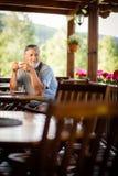 享用他的早晨咖啡的英俊的老人 免版税库存照片