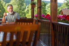 享用他的早晨咖啡的英俊的老人 免版税图库摄影