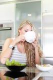 享用健康早餐的年轻美丽的妇女在厨房里 免版税库存图片