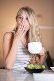 享用健康早餐的年轻美丽的妇女在厨房里 库存图片