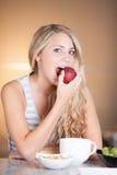 享用健康早餐的年轻美丽的妇女在厨房里 免版税库存照片