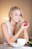 享用健康早餐的年轻美丽的妇女在厨房里 免版税图库摄影