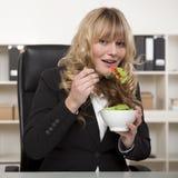 享用健康沙拉的微笑的女实业家 免版税图库摄影