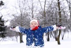 享用冬天和雪的一个小女孩 库存图片