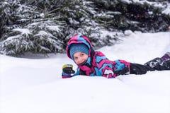 享用冬天和雪的一个小女孩 库存照片