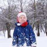 享用冬天和雪的一个微笑的小女孩的一张明亮的正面照片 图库摄影