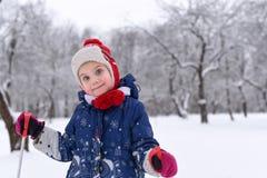 享用冬天和雪的一个微笑的小女孩的一张明亮的正面照片 免版税图库摄影