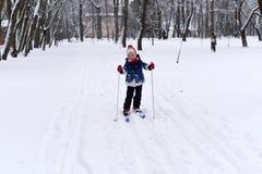 享用冬天和雪的一个微笑的小女孩的一张明亮的正面照片 库存照片