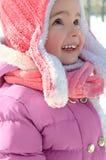 享用冬天和雪的逗人喜爱的小女孩在温暖明亮穿戴了 库存图片