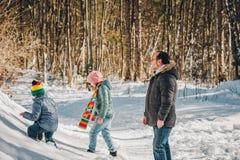 享用冬天森林的父亲和两个孩子画象  免版税库存照片