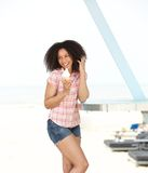 享用冰淇凌的妇女在海滩 库存图片