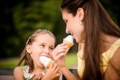享用冰淇凌的母亲和孩子 免版税库存图片