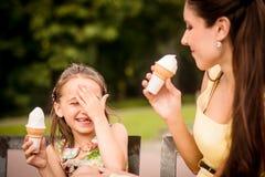 享用冰淇凌的母亲和孩子 免版税图库摄影