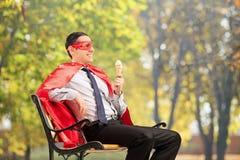 享用冰淇凌的超级英雄供以座位在长凳 库存图片