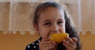 享用可口玉米的逗人喜爱的女孩在一个温暖的夏日 孩子在家吃看照相机的煮沸的玉米 股票视频