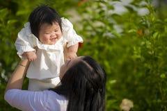 享用和使用与她的女婴女儿的年轻愉快和逗人喜爱的亚裔中国妇女拿着上升在她的胳膊的她 库存图片