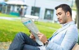 享用和读报纸的英俊的年轻人 免版税库存照片