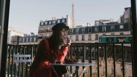 享用咖啡和早餐的愉快的美丽的轻松的旅游妇女在法国早晨咖啡馆露台有埃菲尔铁塔视图 股票录像