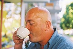 享用咖啡和香烟的秃头 免版税库存照片