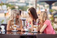 享用咖啡在咖啡馆的三名妇女 免版税库存图片
